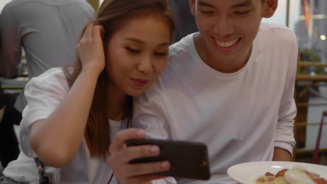 Cute Asian Couple in a Cafe with Smartphone