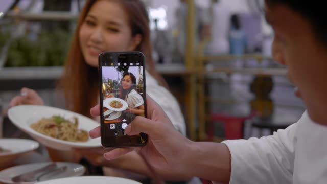 niedliches asiatisches paar im café mit smartphone - teenage friends sharing food stock-videos und b-roll-filmmaterial