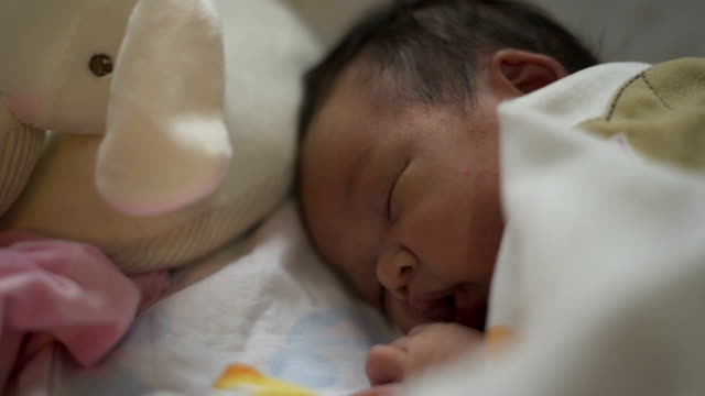 Cute Asian infant sleeping in bed. video