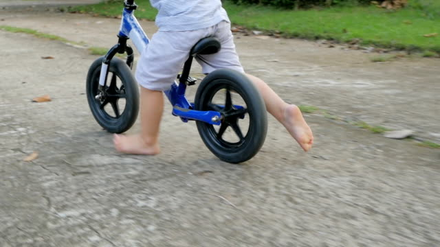 Cute asian little child boy having fun to ride a bike with bare feet. Child learns to keep balance while riding a bicycle. video