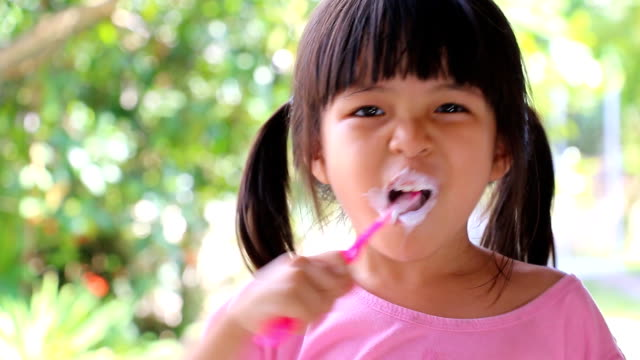 Cute Asian Little Girl Brushing Teeth video