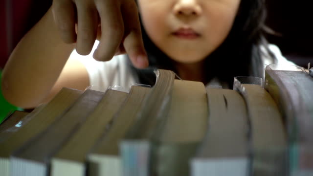 Cute asian little girl is finding a book on bookshelf in the library video