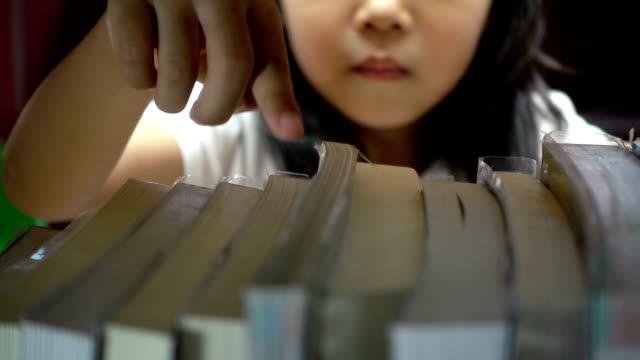 stockvideo's en b-roll-footage met leuke aziatische meisje is het vinden van een boek over de boekenkast in de bibliotheek - literatuur