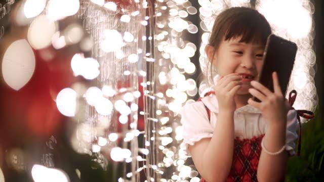 süße asiatische kleine mädchen mit smartphone in weihnachtsfest - weihnachtsstrumpf stock-videos und b-roll-filmmaterial