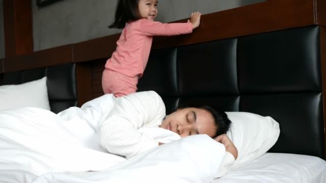 söt asiatisk liten flicka vaknar hennes mamma upp medan liggande på sängen hemma på morgonen. - cosy pillows mother child bildbanksvideor och videomaterial från bakom kulisserna