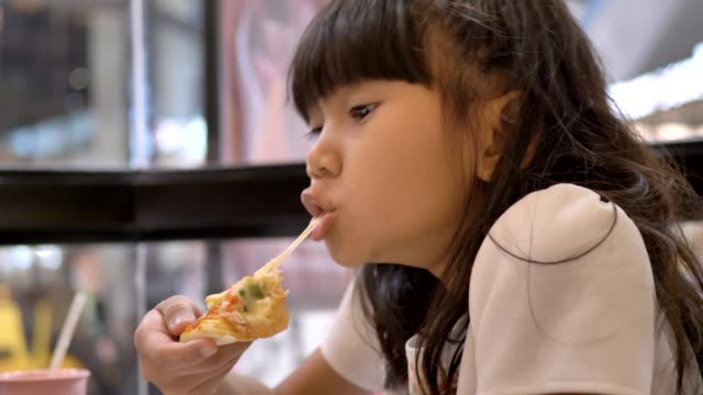 vídeos de stock e filmes b-roll de cute asian little girls eating pizza. - pizza