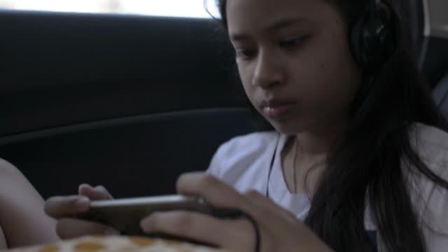 söt asiatisk ung flicka bär hörlurar och använda mobiltelefoner under resan i en bil. allvarliga kvinnliga tonåring spelare spelar online-spel medan du sitter i baksätet på en bil. - människorygg bildbanksvideor och videomaterial från bakom kulisserna