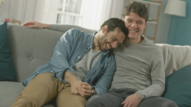 Cute Attractive Male Gay Couple Sit Together on a Sofa at Home. Boyfriends are Hugging and Embracing Each Other. They are Joyful and Laughing. They are Casually Dressed and Room Has Modern Interior. video