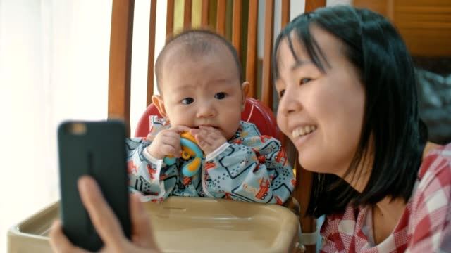 Cute baby boy(6-11 months) and young mom taking selfie with smartphone camera laughing