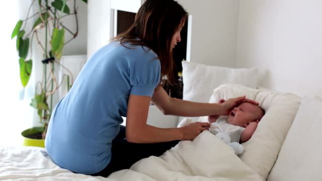 Cute baby boy, lying in bed with cold and fever, mom checking on him. Mother taking care of her sick baby, soothing him video