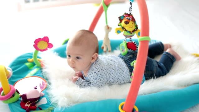 vídeos de stock, filmes e b-roll de menino bonito no ginásio colorido, brincar com brinquedos em casa, bebê atividade e peça centro de desenvolvimento infantil precoce de suspensão. crianças brincando em casa - mobile