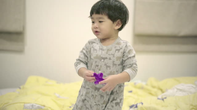 cute baby boy playing with plastic toys - solo neonati maschi video stock e b–roll