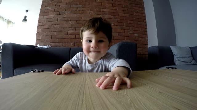 vídeos de stock e filmes b-roll de um bonito bebê menino tentar alcançar algo - coffee table
