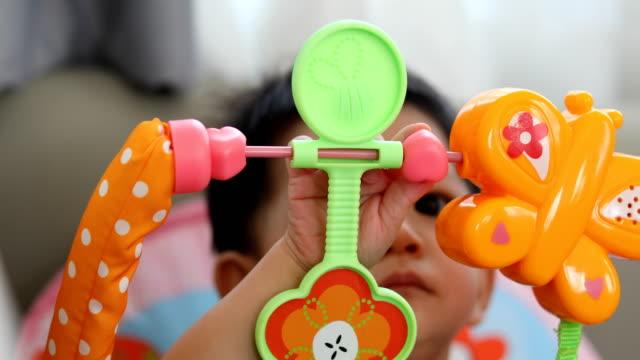 vídeos de stock, filmes e b-roll de menino bonito, usando o dedo da mão jogando brinquedo colorido sobrecarga pendurado na sala de berçário - comodidades para lazer