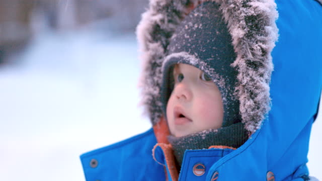 Cute baby boy wearing fur coat during snowstorm video