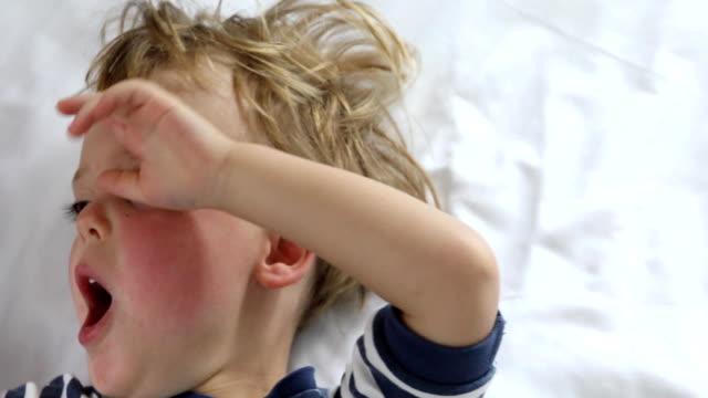 carino bambino sbadiglia sul letto con stanchezza - sonnecchiare video stock e b–roll