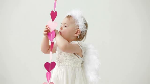 Süßes baby Mädchen gekleidet wie angel spielen mit Papier Herz – Video
