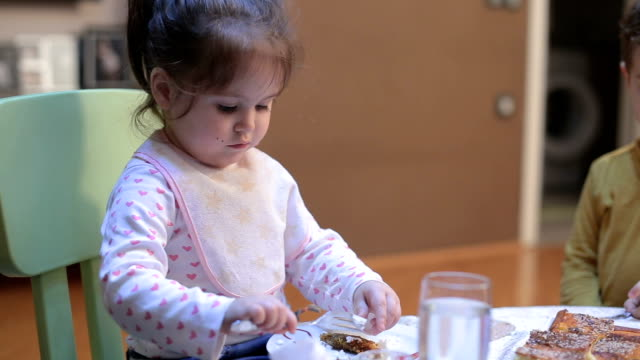 Cute baby girl eating at table with fork video