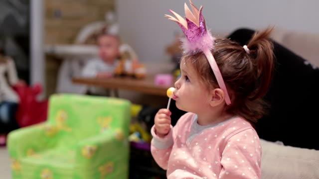 可愛的小寶貝女孩吃舔棒棒糖 - 波板糖 個影片檔及 b 捲影像
