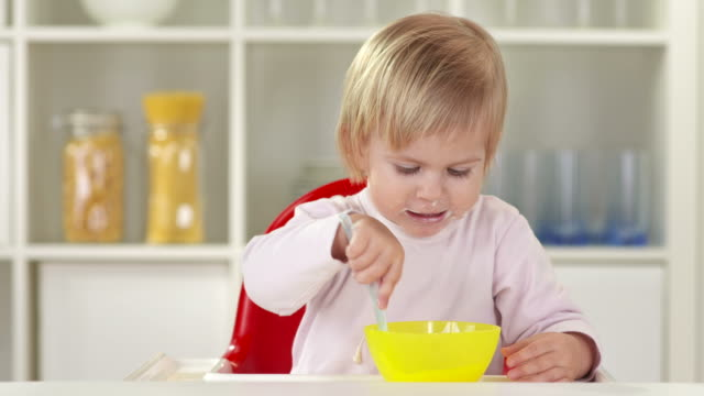 HD: Cute Baby Girl Eating With Spoon HD1080p: Adorable little baby girl eating mashed food with spoon while sitting in a highchair. less than 10 seconds stock videos & royalty-free footage