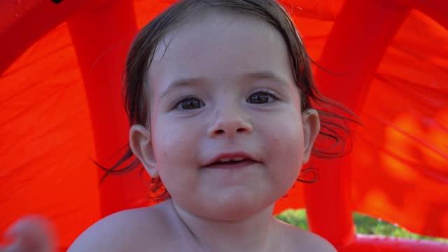 Cute baby girl enjoying the day in a swimming pool having fun