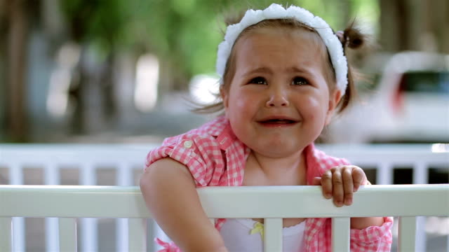 cute baby girl in plaid shirt is sad , baby is crying video