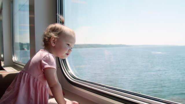 söt baby flicka tittar ut färja fönstret - människohuvud bildbanksvideor och videomaterial från bakom kulisserna