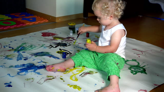 Cute baby girl painting on white paper on the floor at home. video