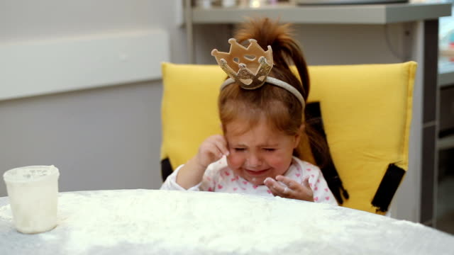Cute baby girl playing with flour on a table and wearing a crown video