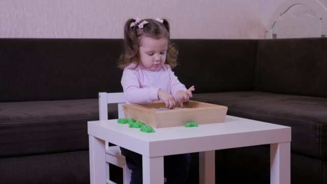 Cute baby girl playing with kinetic sand at home.