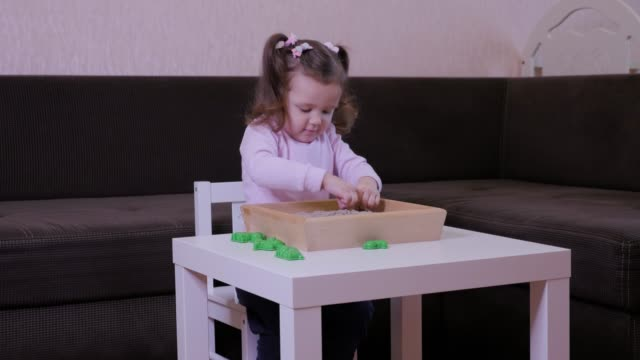Cute baby girl playing with kinetic sand at the table