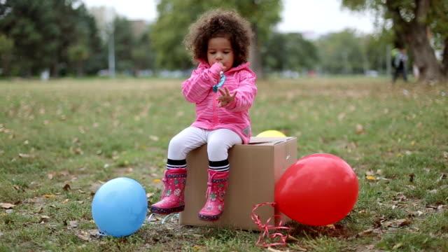 niedlichen Mädchen sitzen auf einem Karton und Partei Horn bläst – Video
