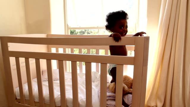 vídeos de stock, filmes e b-roll de bonita menina do bebê em seu berço olhando para a câmera - objeto manufaturado