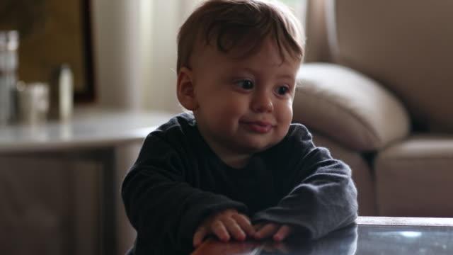 söt baby hålla till bordet, spädbarn pojke lära sig att stå lutar på bordet - förskoleelev bildbanksvideor och videomaterial från bakom kulisserna