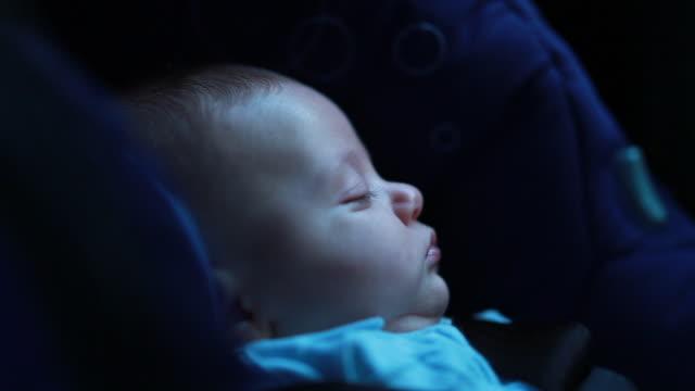 söt bebis spädbarn sover i bilstolen på väg - baby sleeping bildbanksvideor och videomaterial från bakom kulisserna