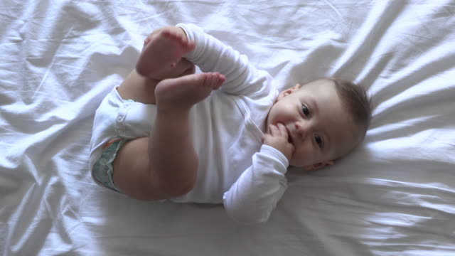 Cute baby infant in bed holding feet being adorable