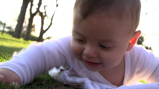 cute baby infant laid in grass outdoors looking to camera smiling - 0 11 mesi video stock e b–roll