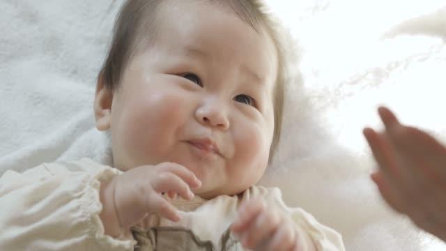 明るい部屋で彼女の背中に横たわっているかわいい赤ちゃん - 母娘 笑顔 日本人点の映像素材/bロール