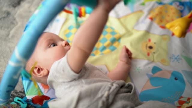 vídeos de stock, filmes e b-roll de bebê fofo brincando em playmat com celular pendurado - mobile