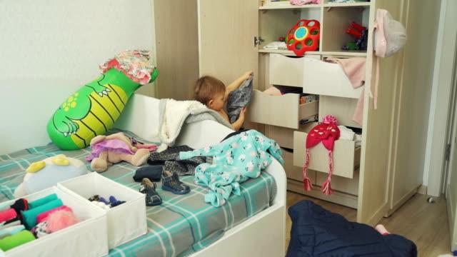 vídeos de stock, filmes e b-roll de bebê bonito que classifica para fora a roupa no quarto desarrumado - desarrumado
