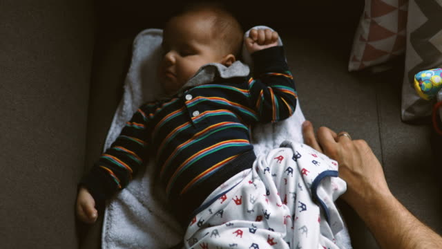 cute baby stretching in his sleep - padre single video stock e b–roll
