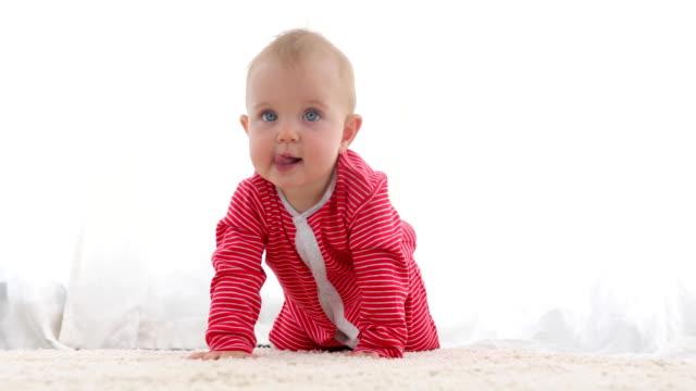 cute baby with bright blue eyes crawling - abbigliamento da neonato video stock e b–roll