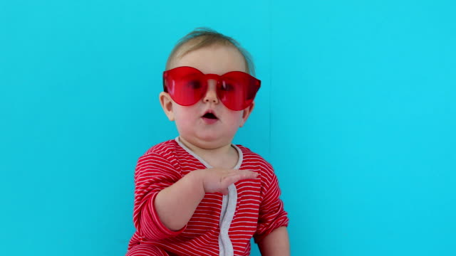 Cute baby with child in red sunglasses