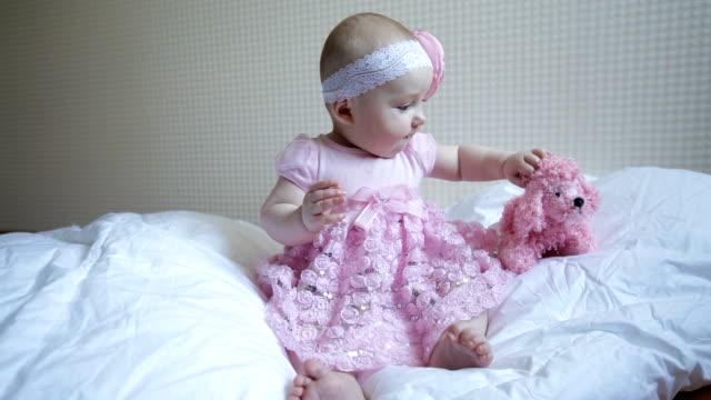söt vacker baby flicka sitter på en säng i rosa klänning - endast flickor bildbanksvideor och videomaterial från bakom kulisserna