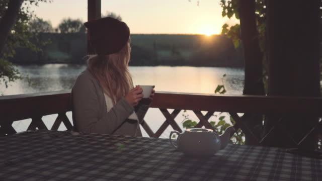 stockvideo's en b-roll-footage met leuk, mooi jong meisje is het drinken van thee in een prieel in de buurt van een prachtig meer op zonsondergang schot in slow motion - christmas cabin
