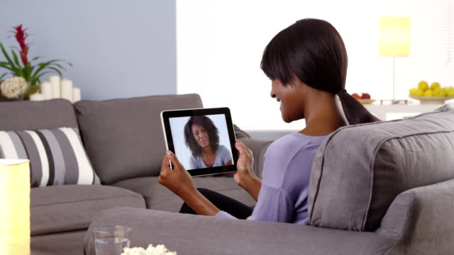 Cute black woman talking with friend on tablet video