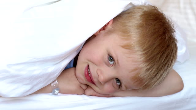 a cute blond boy on a bed under a white blanket, his head covered with a blanket - 2 3 anni video stock e b–roll