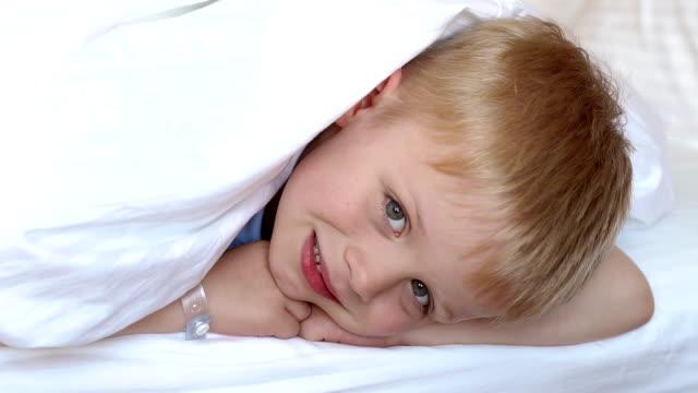 ein niedlicher blonder junge auf einem bett unter einer weißen decke, sein kopf mit einer decke bedeckt - 2 3 jahre stock-videos und b-roll-filmmaterial
