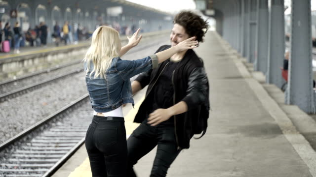 Cute blonde girl looking for boyfriend then kissing him and showing her love in train station video