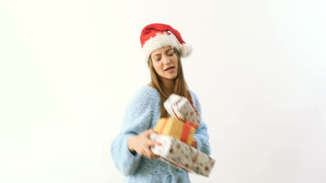 Cute blonde in santa's hat dancing with festive gifts at a white background video